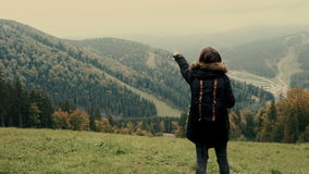 Young girl hiker shows hand on the misty mountain landscape with evergreen conifers. Lifestyle adventure. Back view, toning, 4k stock video footage
