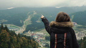 Young girl hiker shows hand on the misty mountain landscape with evergreen conifers. Lifestyle adventure. Back view, toning, 4k stock footage