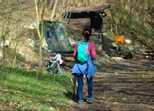 Young girl hiking in a forest with a baby buggy in the background royalty free stock photos