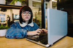 Young girl hipster glasses uses the laptop in a beautiful cafe. Young girl hipster uses a laptop and drinking a hot drink in a nice cafe Royalty Free Stock Photos