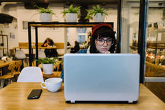 Young girl hipster looks with interest at his laptop and drinking hot d drink in a nice cafe. Young hipster girl looking with interest at a laptop in a beautiful Royalty Free Stock Photography