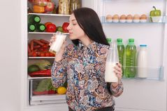 Young girl hold bottle of milk, standing near the open fridge royalty free stock photo