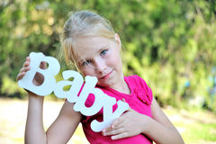 Young girl hold wooden decoration. Handmade word baby near fase Royalty Free Stock Image