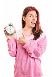 Young girl holding an alarm clock and thumbs up. When timing is right. Young girl in pyjamas holding an alarm clock, isolated on white background stock images