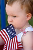 Young girl holding an American flag and riding in red wagon having fun in the park for July Fourth Royalty Free Stock Photography