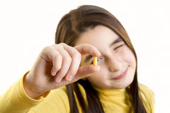 Young girl holding and analizing capsule Royalty Free Stock Image