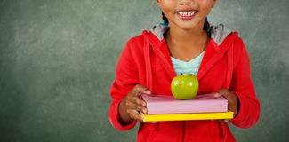 Young girl holding apple and books Stock Photos
