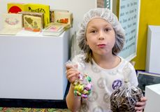 Young girl holding bags of candy at candy factory tour. A young girl in a hair net holds bag of candy after touring a local candy factory Royalty Free Stock Images