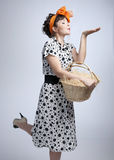 Young girl holding a basket and sending an air kiss Royalty Free Stock Image