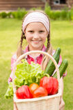Young girl holding basket of vegetables and looking at camera Stock Photography