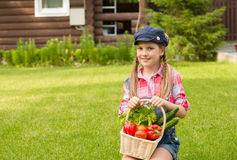 Young girl holding basket of vegetables and looking at camera Stock Image