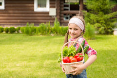 Young girl holding basket of vegetables and looking at camera Royalty Free Stock Photo