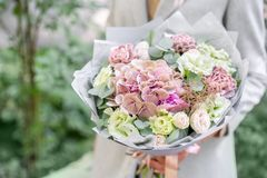 Young girl holding a beautiful spring bouquet. flower arrangement with hydrangea and garden roses. Bright dawn or sunset. Young girl holding a beautiful spring stock photo