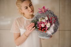 Girl holding a spring composition of different colour flowers, berries and feather. Young girl holding a beautiful spring composition of different colour flowers stock photography
