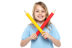 Young girl holding big red and yellow pencils Stock Photography