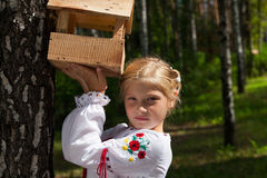 Young girl holding a bird feeder Stock Photos
