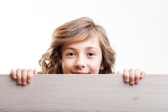 Young girl holding board. Young blond haired girl hiding and holding painted board smiling and looking stock photos