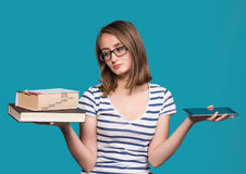 Young girl  holding a book in one hand and a tablet-pc in the ot Stock Photos