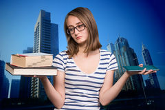 Young girl holding a book in one hand and a tablet-pc in the oth. Pretty young girl holding a book in one hand and a tablet-pc in the other Royalty Free Stock Images