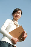 Young   girl holding books with blue sky Royalty Free Stock Photography