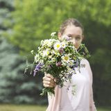 A young girl holding a bouquet of wildflowers in hands royalty free stock photos