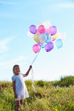 Young Girl Holding Bunch Of Colorful Balloons Outdoors Royalty Free Stock Image