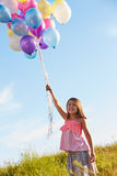 Young Girl Holding Bunch Of Colorful Balloons Outdoors Royalty Free Stock Photography
