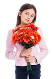 Young Girl Holding a Bunch of Flowers. Beautiful young girl looking at camera while holding a bunch of artificial flowers. Isolated on white background Royalty Free Stock Photography