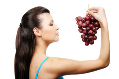 Young girl holding bunch of grapes Stock Photo