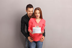 Young girl holding a cake with her boyfriend Stock Photography