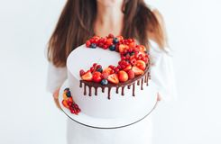 Young girl holding a cake. Cake with white cheese cream, decorated with ganache and red berries on a white stand royalty free stock image