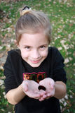 Young Girl Holding Caterpillar in Fall royalty free stock photography