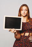 Young girl holding a chalkboard. Royalty Free Stock Photo
