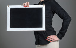 Young girl holding chalkboard. Energetic and sporty young girl holding chalkboard with one hand. Business woman or waitress in a restaurant with black collared Royalty Free Stock Image