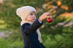 Young girl holding Christmas bauble. A Young girl decorating a fir-tree outdoor Stock Photography