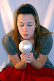 Young Girl Holding a Christmas Decoration Bulb. A young lady looks at an ornament Stock Image