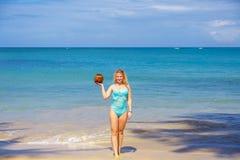 Girl with coco on the beach stock photos