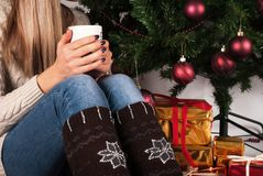 Young girl holding coffee cup in hand and legs with warmers and Christmas tree and gift box in background. Young female legs with warmers on floor carpet holding Royalty Free Stock Photo