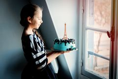 Girl holding a cream cake with Eiffel tower royalty free stock image