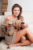 Young girl holding a cup of coffee and a remote co Royalty Free Stock Photo
