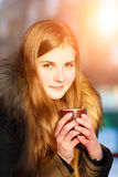 Young girl holding cup of coffee in winter park Stock Image