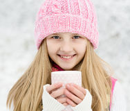 A young girl holding a cup of hot drink and smiling Stock Images