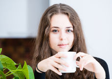 The young girl is holding a cup. In the kitchen Royalty Free Stock Image