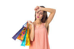 Young girl holding a different packages of stores and second hand keeps near the head isolated on white background Stock Photography