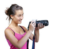 Young girl, holding a digital camera. Young girl, with pink T-shirt, holding a digital camera, isolated on a white background royalty free stock image