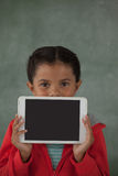 Young girl holding digital tablet against her face. Young girl holding digital tablet in front of her face against chalk board royalty free stock images