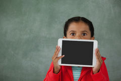 Young girl holding digital tablet against her face. Young girl holding digital tablet in front of her face against chalk board stock photo