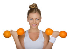 Young girl holding dumbbells from ripe oranges Stock Images