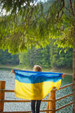 Young girl holding a flag of Ukraine on lake. Young girl holding a flag of Ukraine on synevir lake in Ukraine Stock Photography