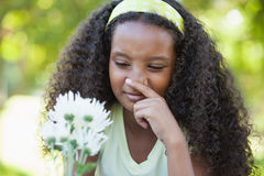 Young girl holding a flower and covering her nose in the park Stock Photography